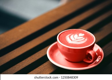 Cup of Living Coral cappuccino on wooden background. Color of the year 2019 concept.