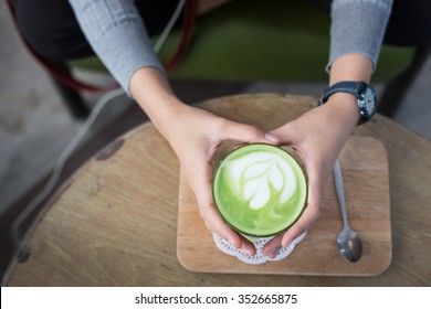 Cup of Matcha Green Tea in woman hand, Greenery pantone