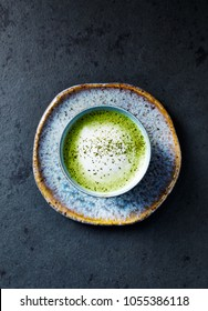 Cup of Matcha Latte on stone background; seen from above