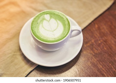 Cup of matcha latte on wooden background and a beige napkin in a cafe with copy space. High quality photo