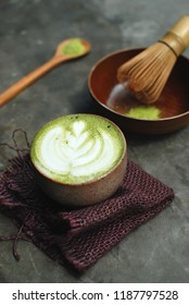 a cup of matcha latte served with a Japanese traditional wooden spoon