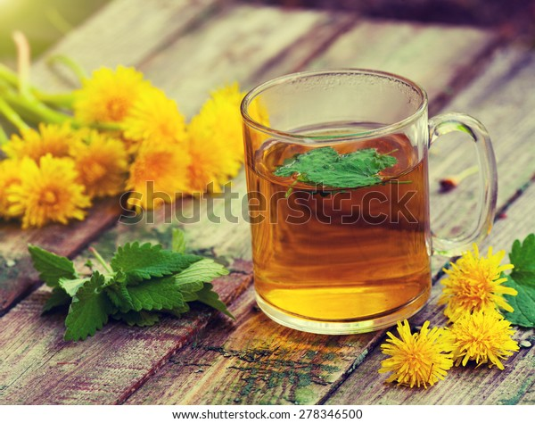 A cup of melissa herbal tea on a wooden table