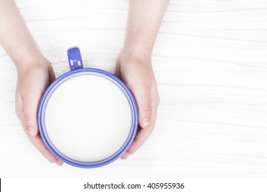 Cup of milk in child hands, top view closeup