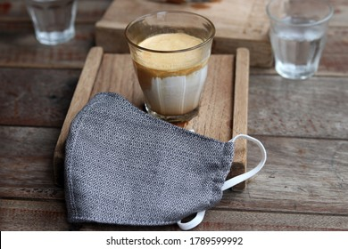 A cup of milk coffee named Dirty Coffee menu and blurred cloth mask on wooden table background. Lifestyle and consumer concept in the New Normal after Covid-19 / Coronavirus pandemic.