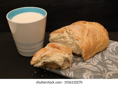 Cup of milk with fresh loaf hunk on gray towel. Black background.
