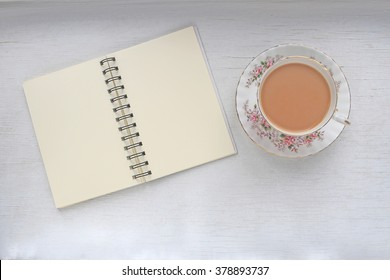 Cup of milk tea in a vintage cup and saucer, and notebook with blank pages.