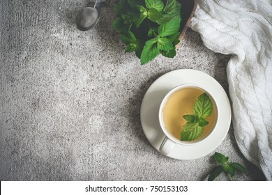 cup of mint tea, fresh mint leaves and a rug on a gray background