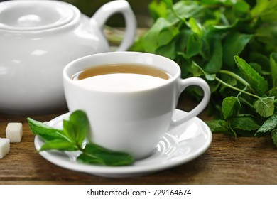 Cup of mint tea on wooden table