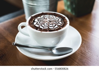 cup of mocha coffee on wooden table in coffee shop.