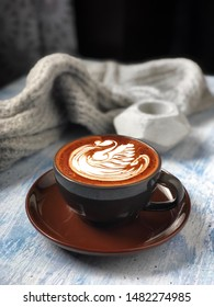 Cup of mocha latte with swan latte art on wooden table