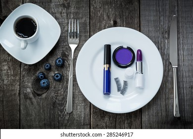 A cup of morning coffee,  lipstick, eyeshadow and fake eyelashes on plate on old wooden board, beauty concept of purple colors