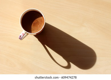 Cup of morning coffee with milk. Natural sunlight