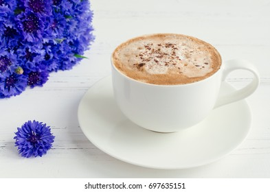 A cup of morning drink cappuccino with whipped cream and bouquet of blue cornflowers on white wooden table.