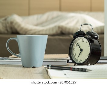 Cup mug and book, pencil, retro alarm clock on the table in bedroom.