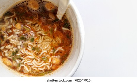 A cup of noodle on the white background . A cup of noodle is a easy food to cooking for the people who do not have time to cook but this menu is unhealthy. At the Asia a cup of noodle is a popular.