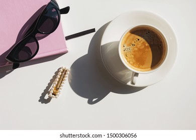 Cup, notepad and sunglasses on the white table on sunny day. Modern trendy style flat lay with natural light