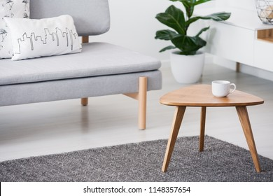 Cup on a wooden coffee table and blurry background with graphic pillows on a gray sofa in a white living room interior
