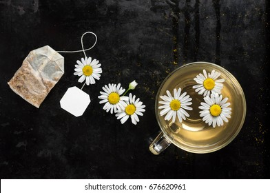 Cup of organic, anti-inflammatory, antimicrobial herbal tea with fresh chamomile flowers on dark background. Top view