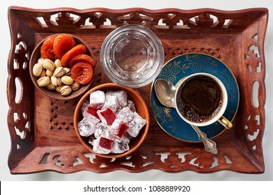 Cup of oriental black coffee and glass of water with traditional eastern sweets rahat lokum, pistachios and dried apricots on wooden tray. Breakfast concept on white background, top view