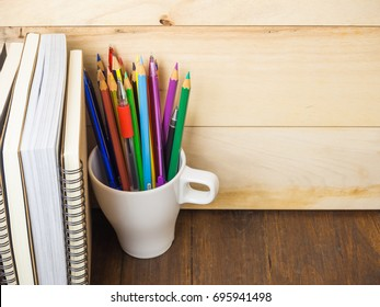 A cup of pencils & pens with many books on wooden table, education concept.