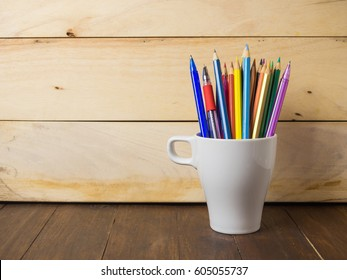 A cup of pencils & pens on wooden table, education concept.