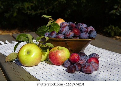 Cup of plums with apples on the desk in the garden at summertime