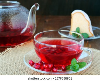 Cup of pomegranate tea with mint and tea pot with a piece of cake over burlap on dark background