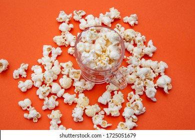 cup with popcorn on orange color background