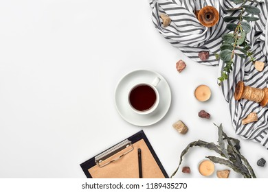 Cup with a ready tea on a white table. Top view, flat lay. Copy space