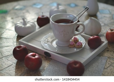 Cup with red fruit tea, cookies on a white vintage tray among porcelain fruits and sweet red autumn apples on a mosaic table in backlit. Autumn-winter still life