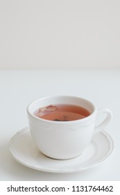 Cup of red herbal tea on white table, vertical photo. Hibiscus tea with rose petals flavor