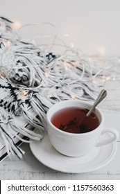 Cup of red hibiscus tea, book, lights for home decoration and woolen knitted blanket on wooden table, vertical photo. Hygge concept