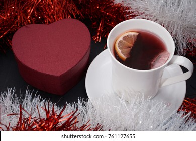 Cup of red tea with lemon slice, present on dark table
