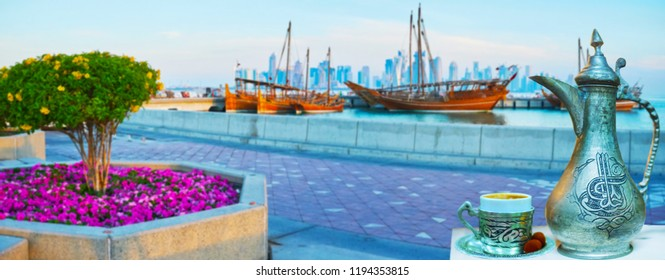 A cup of refreshing coffee, brewed in vintage dallah coffeepot, decorated with Islamic patterns, with a view on Doha harbor full of dhow boats and skyscrapers behind the waters of Persian Gulf, Qatar.