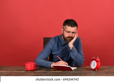 Cup, retro clock and red book on vintage table. Professor with bored face sits at wooden table. Exam and studying concept. Man with beard and glasses writes in notebook on red background