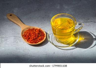 A cup of safflower herbal tea and Safflower, False Saffron, Saffron Thistle in wooden spoon .