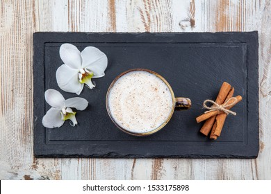 Cup of salep milky hot drink of Turkey with cinnamon powder and sticks healthy spice on white rustic vintage wooden table. Sahlep background.