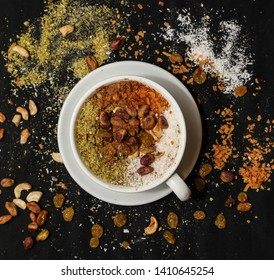 Cup salep (milky traditional hot drink) With Pistachios and Raisins On a black background