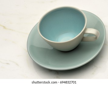 Cup and saucer on white marble background