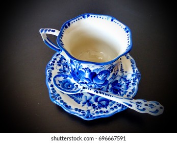 The cup with saucer and teaspoon in Russian traditional Gzhel style on a black background. Gzhel - Russian folk craft of ceramics and production porcelain and a kind of Russian folk painting.
