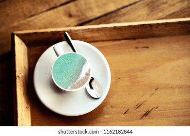 A cup of sea concept. Top view espresso coffee cup with sea waves on wooden background.