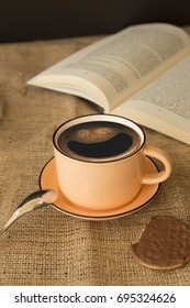 A cup of smiley coffee with a book and cookie on the table