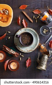 Cup of spiced coffee and fall themed items over dark rustic background. Top view