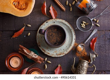 Cup of spiced coffee and fall themed items over dark rustic background