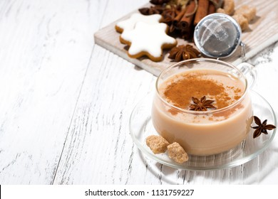 cup of spicy masala tea and Christmas cookies on white background, top view horizontal