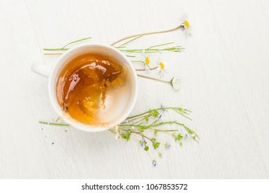 cup of splashing herbal tea on white table