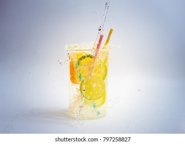 Cup with splashing lime and lemon water and paper straws, selective focus.