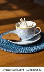 Eine Tasse spritzender Milch und der Keks in der Sonne