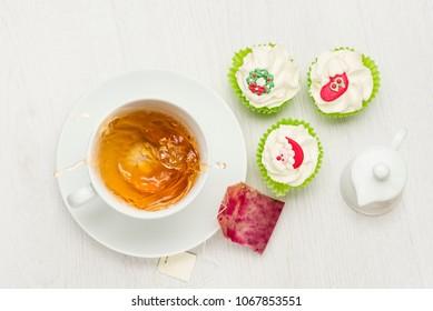 cup of splashing tea on white table with tea bag and christmas cupcakes