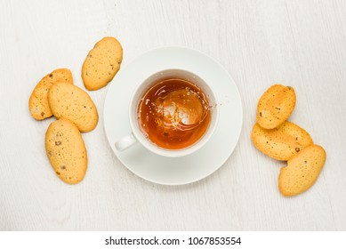 cup with splashing tea on white table with cookies